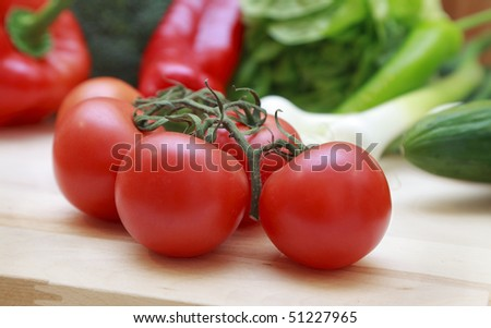 Fresh tomatoes and vegetables on a wooden chopping board.