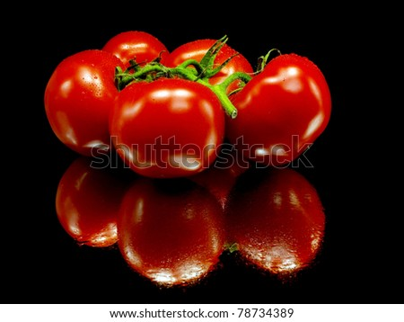 fresh tomatoes on a black background with water drops