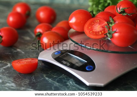 Fresh tomatoes on kitchen scales weighing and measuring