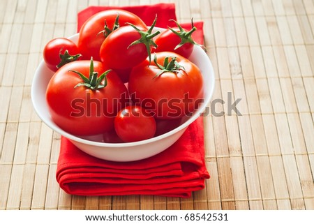 fresh tomatoes on red napkin and bamboo