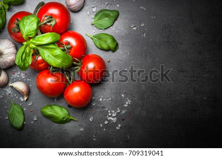 Fresh tomatoes with basil garlic and sea salt on black slate background. Top view with copy space.