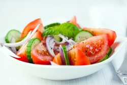 Fresh tomatoes with basil leaves, red onion, cucumber and spices in a ceramic bowl. Symbolic image. Concept for a tasty and healthy appetizer. White wooden background. Close up. Front view.