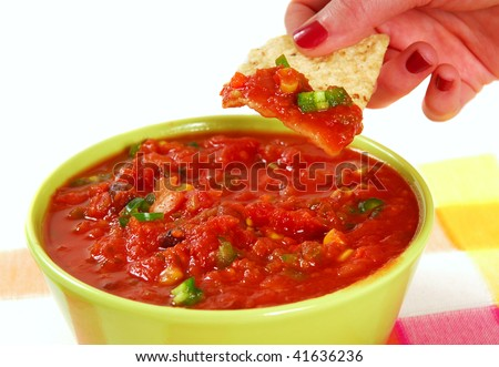 Fresh tortilla chip being dipped into a hot and spicy salsa