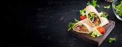Fresh tortilla wraps with ham beef and fresh vegetables on wooden board. Beef burrito. Mexican cuisine. Banner