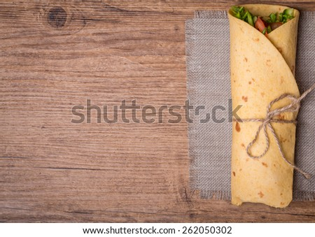 fresh tortilla wraps with vegetables on wooden background top view