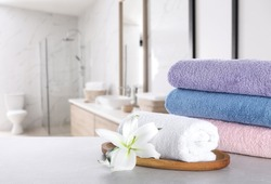 Fresh towels and lily flower on light grey marble table in bathroom. Space for text