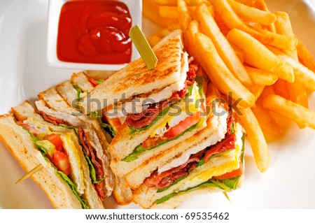 fresh triple decker club sandwich with french fries on side