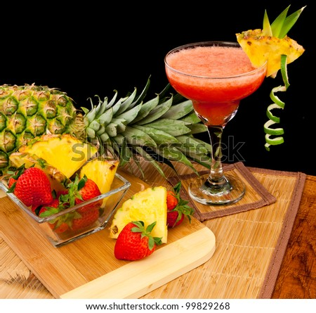 fresh tropical fruit cocktail on a bar top isolated on a black background