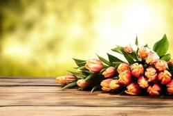 fresh tulips and desk of wood