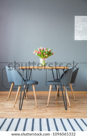 Fresh tulips in glass vase standing on wooden hairpin table in grey dining room interior with carpet #1096065332
