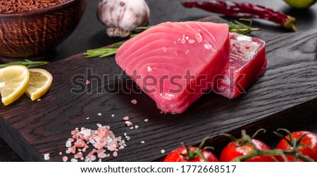 Fresh tuna fillet steaks with spices and herbs on a black background. Preparing tuna for baking Foto d'archivio ©