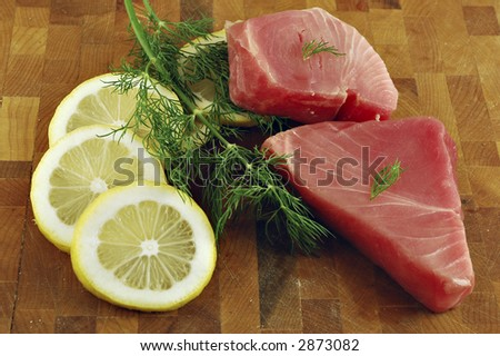 Fresh tuna steaks with lemon and dill on a cutting board