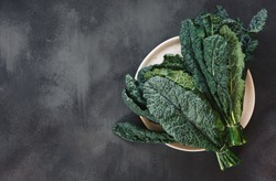 Fresh  Tuscan kale leaves on a white plate and on rustic dark background. Top view, blank space