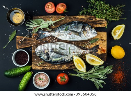 Fresh uncooked dorado or sea bream fish with lemon, herbs, oil, vegetables and spices on rustic wooden board over black backdrop, top view #395604358