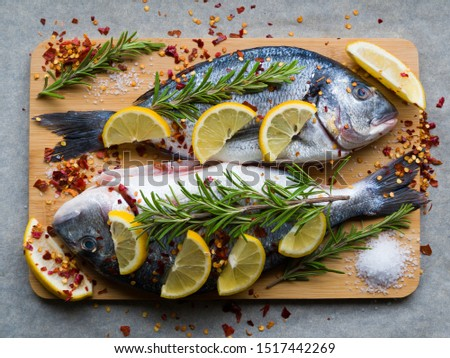 Fresh uncooked dorado or sea bream fish with lemon slices, spices, herbs and rosemary on cutting board. Mediterranean cuisine. Top view