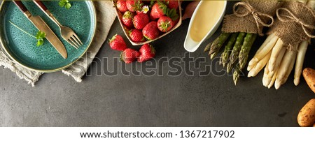 Fresh uncooked green and white asparagus, mayonnaise, potatoes and strawberries with an empty plate and utensils in panorama banner format viewed from above