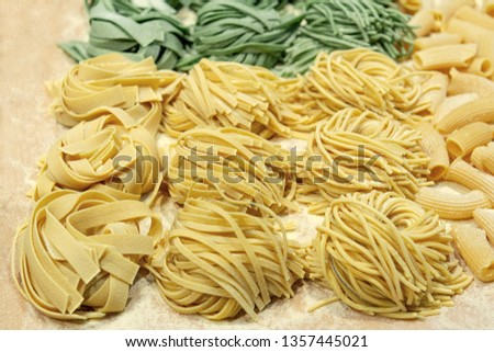 Fresh uncooked homemade pasta with spinach and wheat twisted on the table.