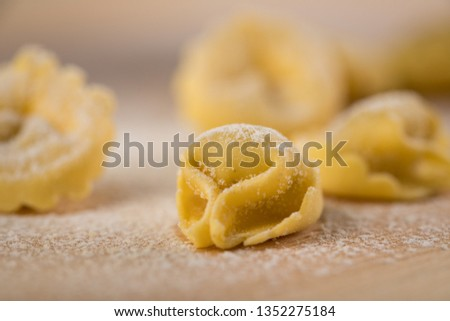 Fresh, uncooked Italian Cappelletti Tortellini pasta with flour and semolina  on wooden board