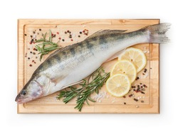 Fresh uncooked pike perch with lemon, rosemary and spice on wooden board isolated on white background with clipping path