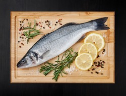 Fresh uncooked seabass with lemon, rosemary and spice on wooden board over black backdground