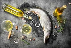 Fresh unprepared pike with white wine. On a rustic background.