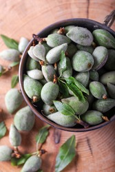 Fresh unripe almonds on the wooden background. Fresh raw green almonds in the metal bowl. Top view.