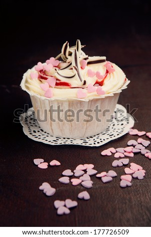 Fresh vanilla cupcake decorated with pink hearts on a old brown background