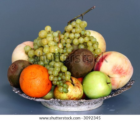 Fresh variety of fruit in basket with water drops
