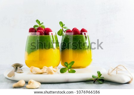 Fresh vegan layered dessert in a glass of colored smoothies of mango and spinach with fresh raspberries and mint.