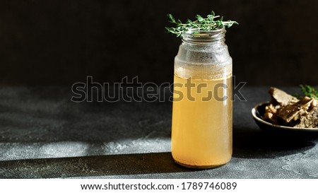 Fresh vegetable bone broth in glass jar with herb on dark gray background. Healthy dieting food are rich in vitamins, collagen and anti-inflammatory amino acids Сток-фото ©