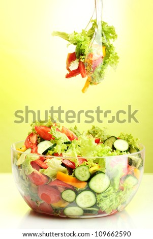 fresh vegetable salad in transparent bowl with spoon and fork on green background