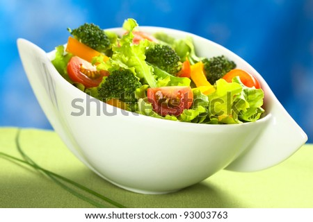 Fresh vegetable salad made of tomato, broccoli, yellow bell pepper and lettuce (Selective Focus, Focus on the tomato and the broccoli in the front)