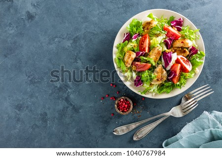 Fresh vegetable salad of tomatoes, cucumbers, italian mix, lettuce and grilled chicken breast. Fried chicken meat, fillet with salad. Healthy food. Flat lay. Top view
