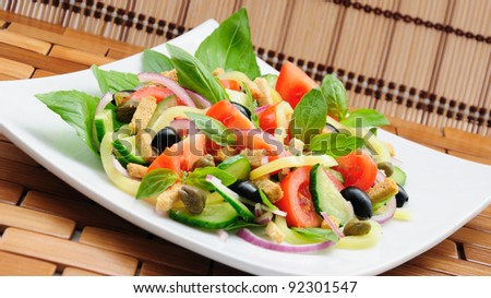 Fresh vegetable salad with basil, capers, olives, marinated with croutons
