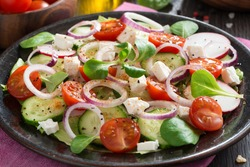 fresh vegetable salad with feta cheese on a plate, close-up, horizontal