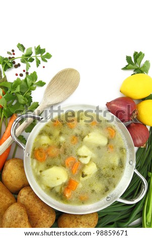 Fresh vegetable soup in a pot with mixed vegetables around it