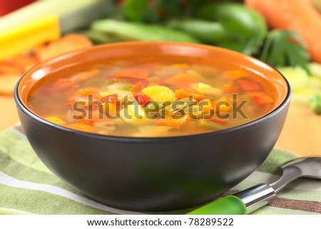 Fresh vegetable soup made of bean, pea, carrot, potato, red bell pepper, tomato and leek in black bowl with ingredients in the back (Selective Focus, Focus on the vegetables in the middle of the soup)