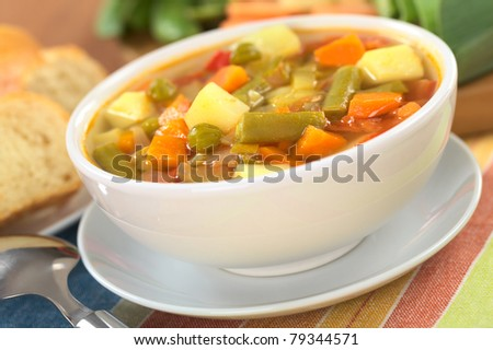 Fresh vegetable soup made of green bean, pea, carrot, potato, pepper and leek with baguette slices and ingredients in the back (Selective Focus, Focus on the vegetables one third into the soup)