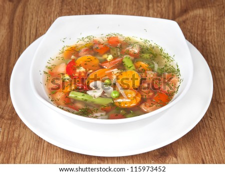 Fresh vegetable soup made of green bean, pea, carrot, potato, red bell pepper, tomato and leek in bowl with parsley in the back