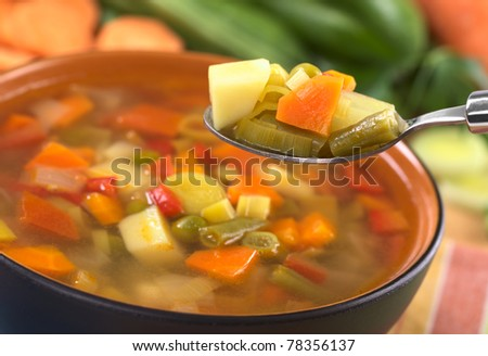 Fresh vegetable soup on spoon made of green bean, pea, carrot, potato, pepper, tomato and leek (Selective Focus, Focus on the carrot, leek and green bean on the spoon) - stock photo