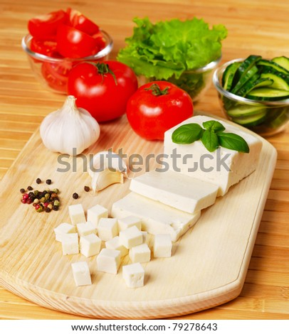 Fresh vegetables and feta cheese on the chopping board