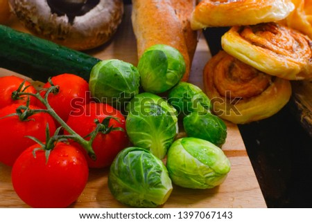 Fresh vegetables and fresh tomato,brussels sprouts, bread, cinnamon rolls, picture placement, still light, shadow #1397067143