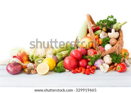 Shutterstock Fresh vegetables and fruit in basket on white background.