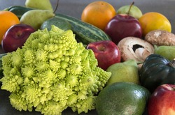 Fresh vegetables and fruits on a table. Close up photo of Romanesco cauliflower, avocado, pears, apples, zucchini and mushrooms. Healthy eating concept.