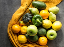 Fresh vegetables and fruits on a table. Yellow and gray textured background. Seasonal organic vegetables from local market. Healthy eating concept.