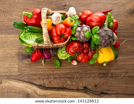 fresh vegetables and herbs in basket on wooden background. raw food. top view. selective focus
