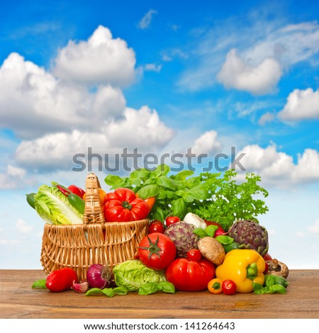 fresh vegetables and herbs on wooden background with beautiful blue sky. shopping basket with organic food ingredients