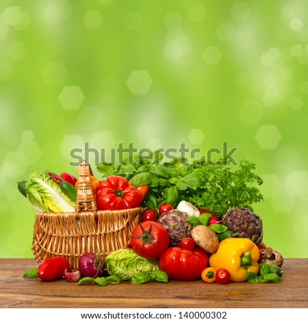 fresh vegetables and herbs on wooden table over nature green background. raw food ingredients. shopping basket