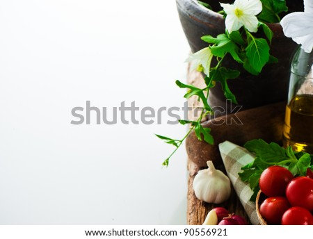 fresh vegetables and olive oil on an old weathered wood with a old mortar in behind over white background