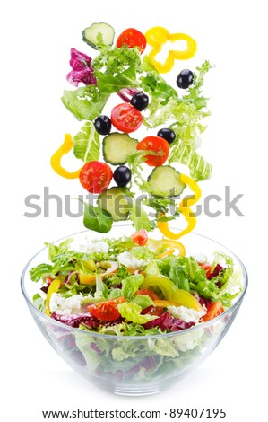 fresh vegetables, as salad ingredients, falling into bowl on white background